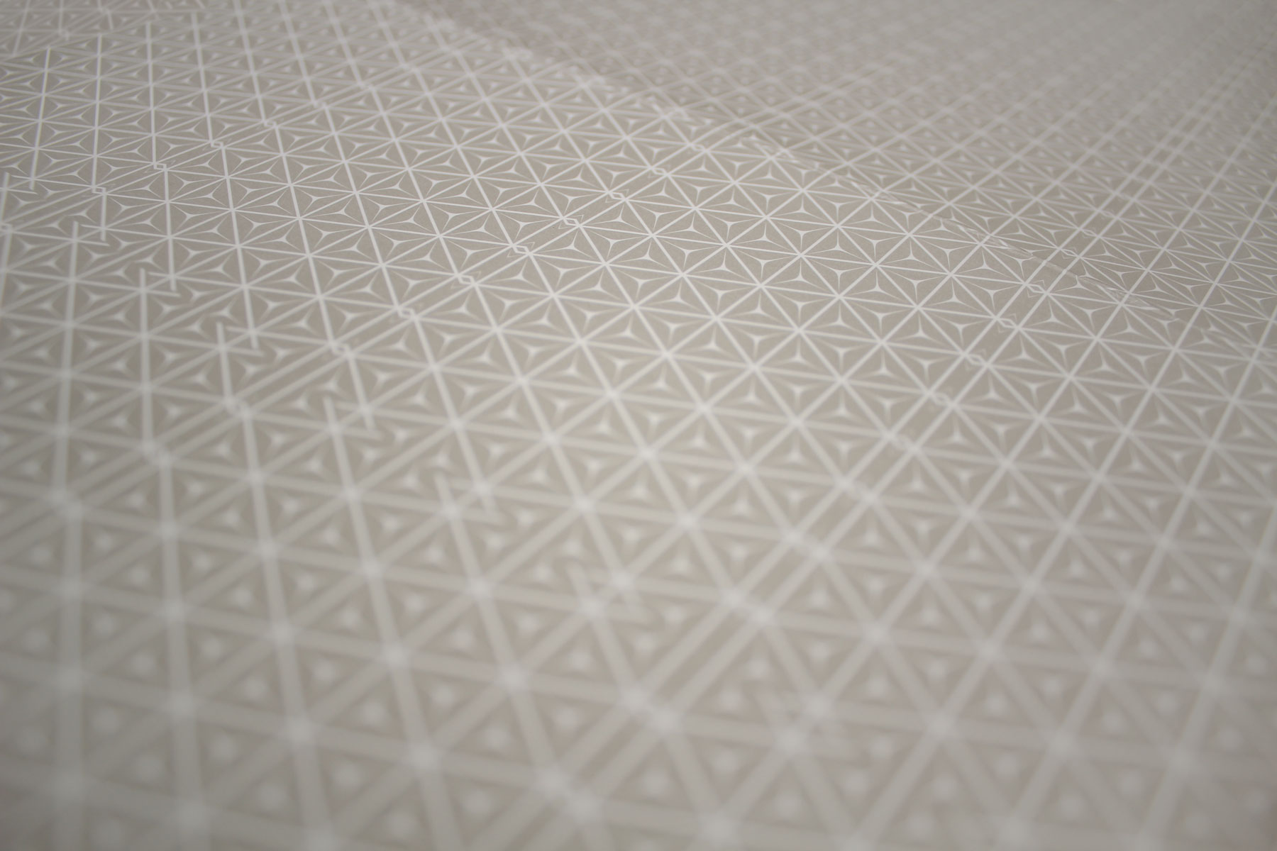 A subtle visual pattern device is used throughout the identity, conveying quality and prestige.